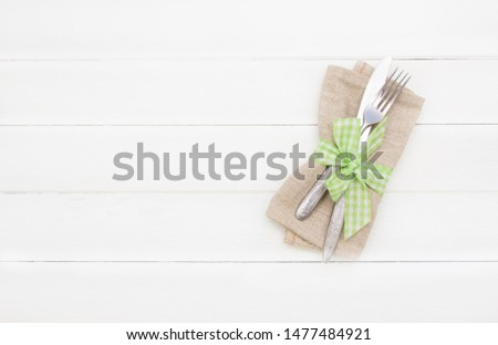 Table setting .Close up Fork and Knife  on  napkin ,empty space. Spring table setting with green ribbon