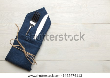 table setting. cutlery. Fork, knife in a blue napkin on a white wooden table. top view