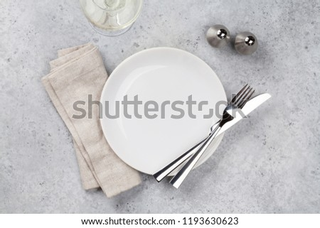 Table setting. Empty plate, knife, fork, wine glass and napkin. Top view and flat lay with copy space