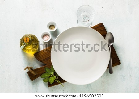 table setting. empty plates, spices, cutlery and olive oil. place to write text. copy space. collage template