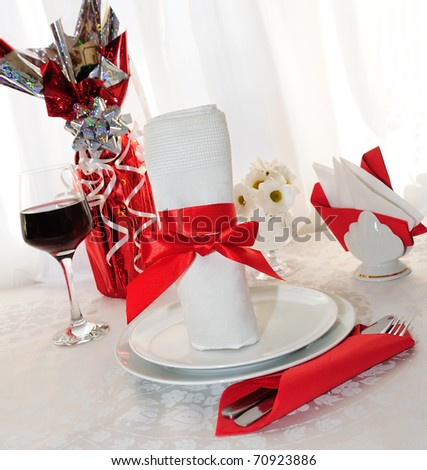 Table setting for a holiday napkin, flowers, wine
