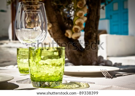 Table setting for al fresco dining in a picturesque village street with olive tree and garlic in the background. - stock photo