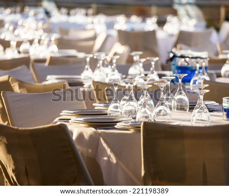 Table setting for an event party at outdoor cafe in the evening light