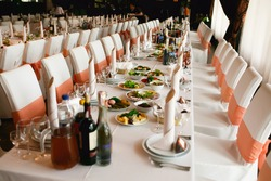Table setting for an wedding reception in orange color