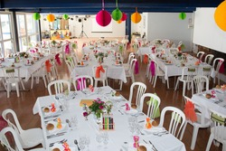 Table setting for an wedding reception in orange, pink and yellow color