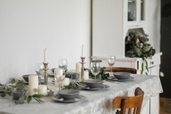 Table setting: gray dishes, white candles, candlesticks, glass goblets, sprigs of eucalyptus on a wooden table with a white tablecloth. Beautiful Scandinavian style interior.