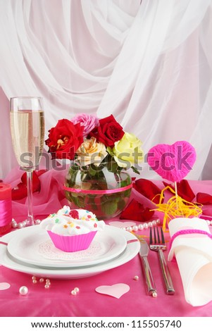 Table setting in honor of Valentine's Day on white fabric background