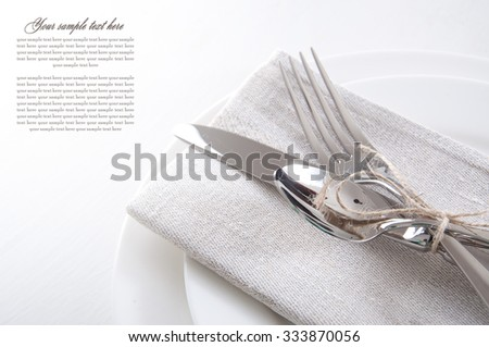 Table setting in white and gray colors with linen napkins and silverware  #333870056