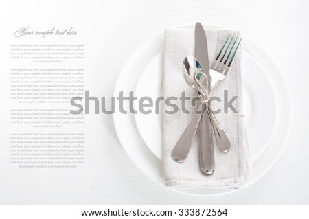 Table setting in white and gray colors with linen napkins and silverware #333872564