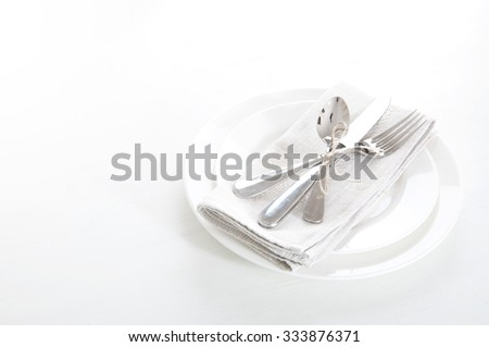 Table setting in white and gray colors with linen napkins and silverware #333876371