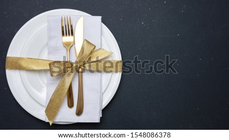 Table setting, luxury, formal. Gold cutlery on white set of dishes, black background, top view Photo stock ©