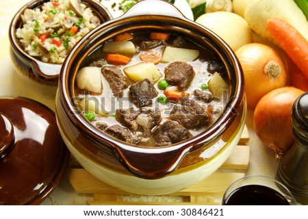 Table setting of freshly baked beef stew with savory rice and seasonal vegetables and herbs.