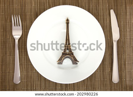 table setting of plate, fork, knife and Eiffel tower knife on dark background