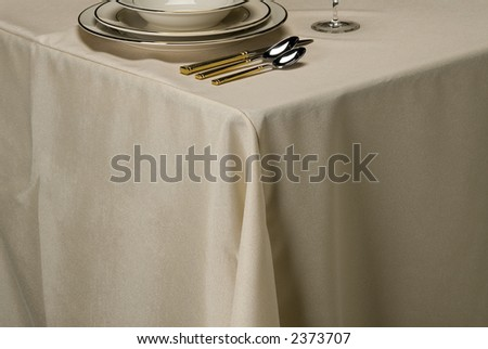 table setting showing linen table cloth, dishes and silverware