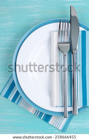 Table setting: white plate, fork and knife with napkins on aquamarine wooden table. Top view point. #258666455
