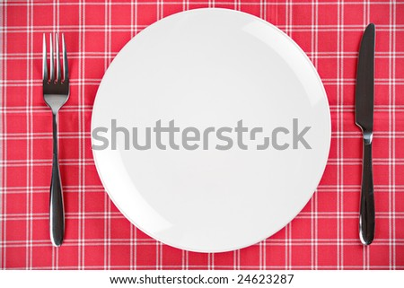 Table setting with an empty plate and fork and knife - stock photo