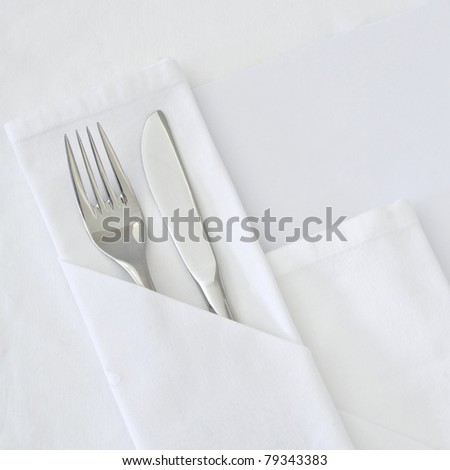 Table setting with blank menu card with white linen