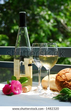 Table setting with chilled white wine and glasses alfresco