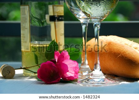 Table setting with chilled white wine and glasses alfresco, closeup