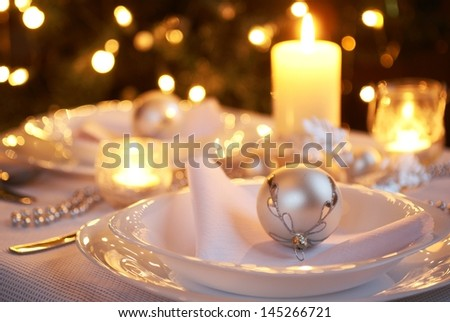 Table setting with Christmas decorations and Christmas tree in a background.