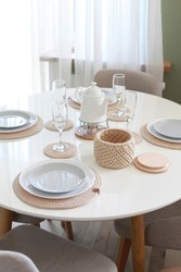 Table setting with dishes and tableware in stylish modern interior. No people. Dining  table with place settings. Plates on knitted napkins, glasses and crochet basket for nuts or fruits.