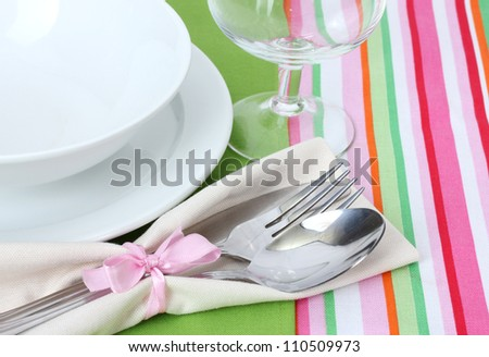 Table setting with fork, spoon, knife, plates, and napkin