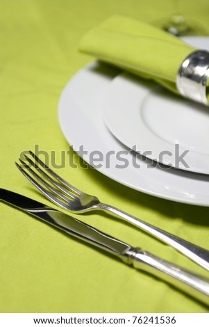 table setting with plates, napkin, silverware and glass on apple green table cloth