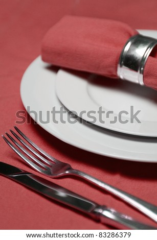 table setting with plates, napkin, silverware in a bright red color