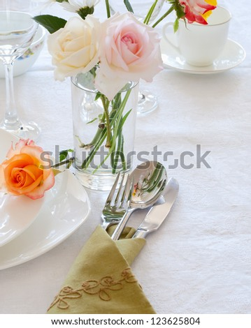 Table setting with plates, silverware and flowers