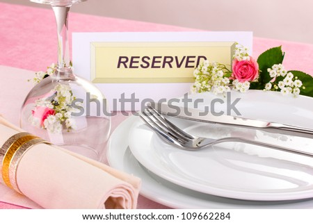 Table setting with reserved card in restaurant