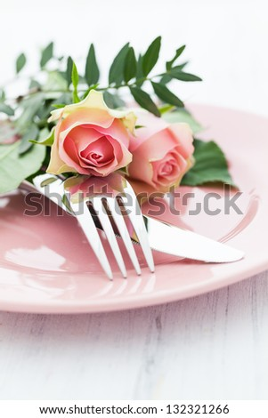 table setting with roses in pink