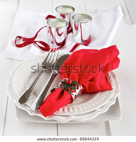Table setting with silverware, red napkin, candles and decoration for Christmas