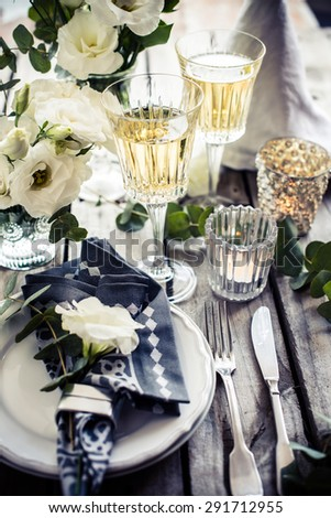 Table setting with white flowers, candles and glasses of champagne on an old vintage rustic wooden table. Vintage summer wedding table decoration.