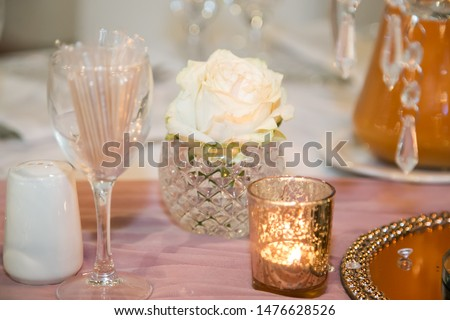 table setting with white rose candle and tooth-pics