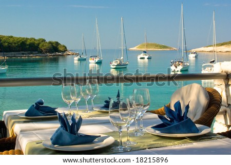 Table settings at restaurant on island's seaside with lagoon