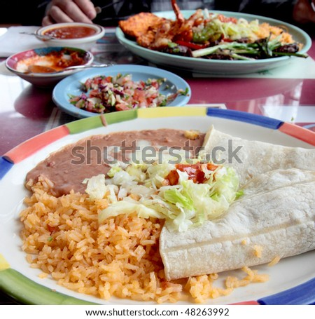 Table spread with tasty tacos,rice,beans, and salsa