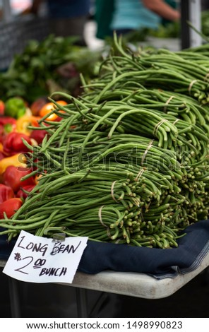 """table stacked with bunches of chinese long beans with sign """"long bean $2 a bunch"""", bundles of green beans at farmers market, organic produce, fresh vegetables, local produce at outdoor market"""