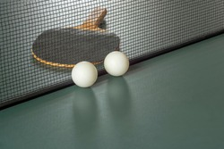 Table tennis attributes: Racket, balls, table with a net.