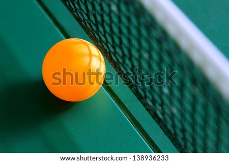 Table tennis ball on table with net