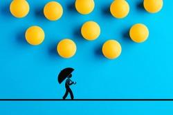 Table tennis balls designed as raindrops are falling on the icon of a man walking with umbrella. Disaster, misfortune, accident, risk or danger concept.