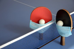 Table Tennis Paddles with ball and medical mask on the blue table tennis table. Fitness during quarantine.