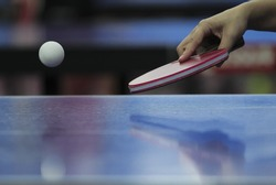Table tennis ping pong paddles and white ball on blue board.