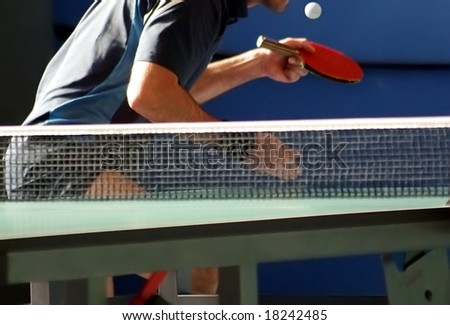 table tennis player serving, focus is on the ball