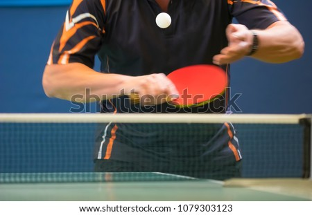 Table Tennis Player serving, motion blur, focus at the ball in the air