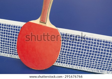 Table tennis racket and net on a blue table tennis table