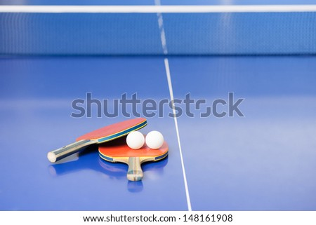 Table tennis rackets. Top view of table tennis rackets and balls lying on the tennis table