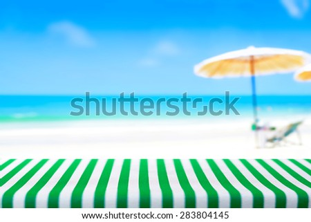 Table top covered with striped tablecloth on blurred beach background, picnic and holiday concepts - can be used for display and montage your products