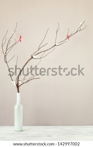 Table top decoration, vase with wooden branch twig with red ribbons, simple elegant rustic holiday festive christmas background