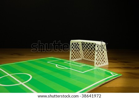 Table Top FootBall Pitch and A white Plastic Goal on A wooden Table
