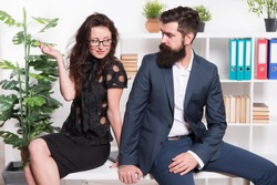 Table top review. Business couple sit on office desk. Staff meeting. Formal meeting. Bearded man and sexy woman in formalwear. Business meeting. Meeting appointment. Job interview. Holding workshop.